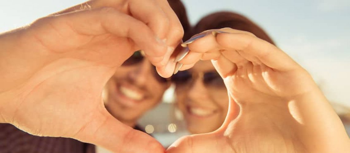 52410143 - happy romantic couple in love gesturing a heart with fingers